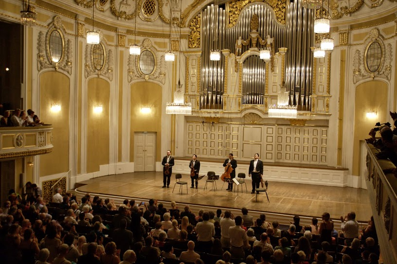 Los integrantes del Cuarteto son principales de fila de la Orquesta Sinfónica Simón Bolívar de Venezuela y grabaron su primera producción discográfica en el 2012 con la Deutsche Grammophon
