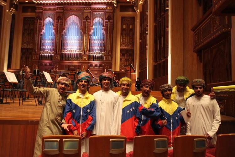 Un grupo de músicos entre el público ataviados en trajes omaníes y con chaquetas tricolor