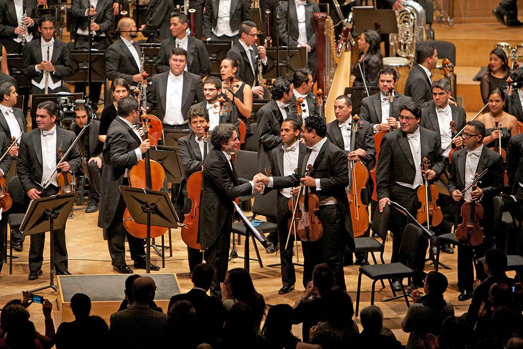 El director Dudamel felicita a la primera viola, Ismel Campos, luego del segundo concierto en el centro cultural Bozar