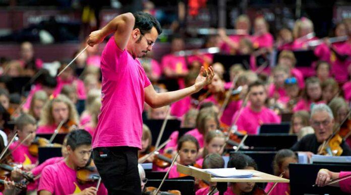 Ron Álvarez dirigiendo a más de 500 jóvenes en el Festival Side By Side. El director de 30 años creó en junio la Orquesta de Sueños de El Sistema Suecia. Credit Cortesía de Lisa Thanner/El Sistema Suecia